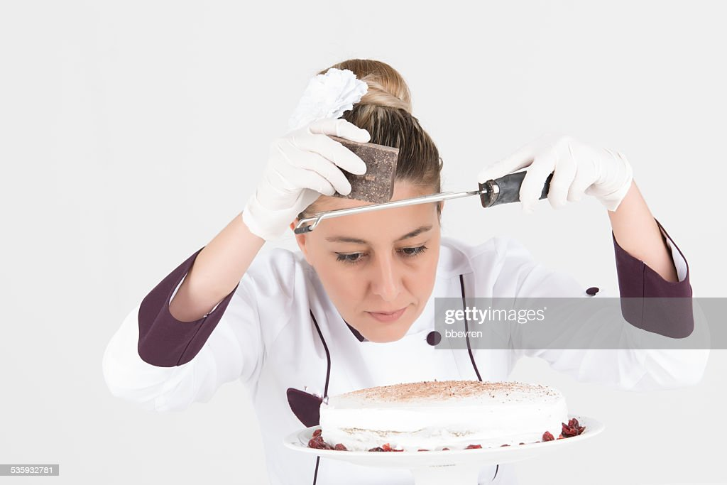 Focused cook chef grating chocolate to the white creamy cake : Stock Photo