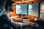 Focused developer coding on computer monitors working late in office