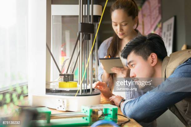Focused engineers prototyping project on 3D printer