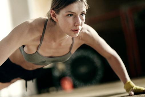 Focused female boxer doing push-ups - gettyimageskorea