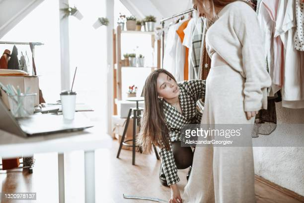 focused female clothing designer measuring customer's leg length - length stock pictures, royalty-free photos & images