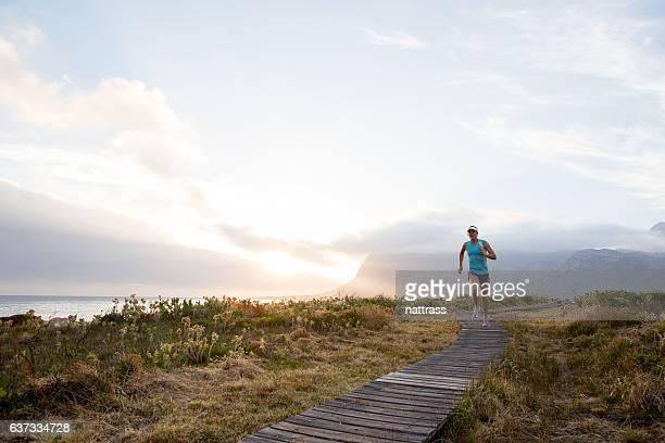 Focused female runs along a beautiful coastal path