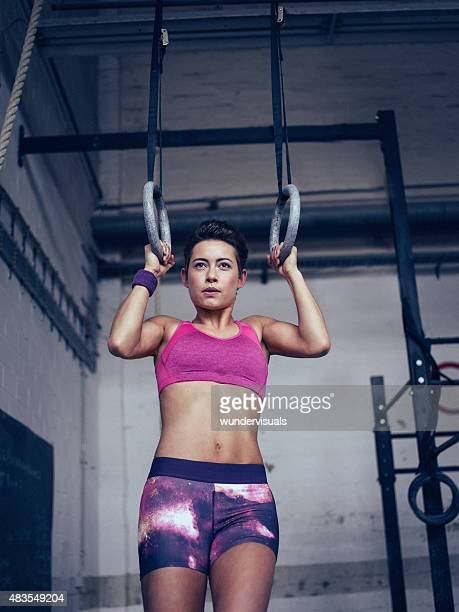 Focused girl exercising with gymnastic rings in a gym
