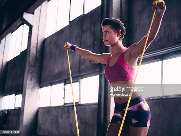 フォーカスガールピンクのスポーツウェアのエクササイズにイエローチューブエクササイズ