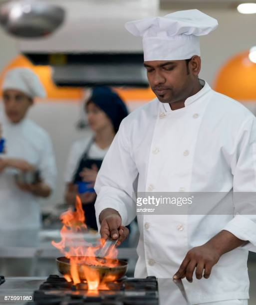 Focused indian chef doing flambe on a meat using a frying pan