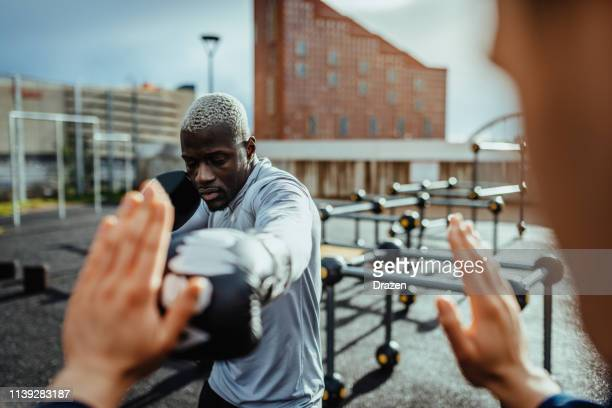 focused kick-boxer exercising with sparing-partner outdoors on cloudy day. - boxing stock pictures, royalty-free photos & images
