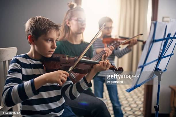 focused kids rehearsing music together - stringed instrument stock pictures, royalty-free photos & images