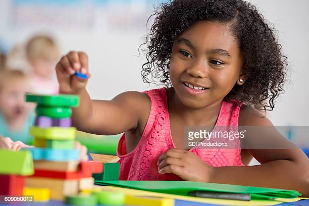 Focused little girl plays with blocks