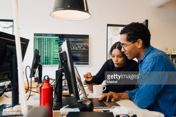 focused male and female engineers coding over laptop on desk in office - engineer stock pictures, royalty-free photos & images