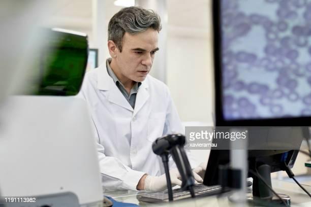 patólogo masculino enfocado en el trabajo en el laboratorio de análisis clínico - laboratorio clinico fotografías e imágenes de stock