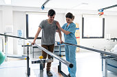 Focused male patient at physical therapy walking with the help of parallel bars and therapist next to him