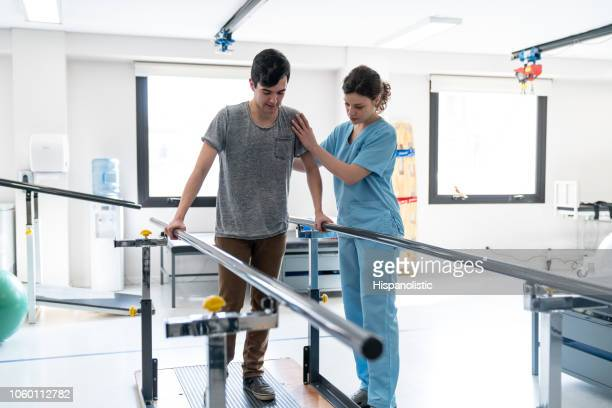 focused male patient at physical therapy walking with the help of parallel bars and therapist next to him - crutch stock photos and pictures