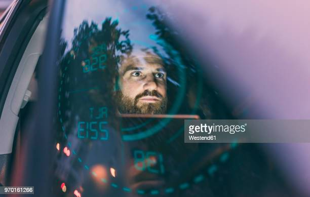 Focused man in car at night surrounded by dashboard projection