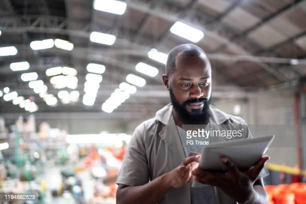 gerente focalizado que usa a tabuleta digital em uma fábrica - focus concept - fotografias e filmes do acervo