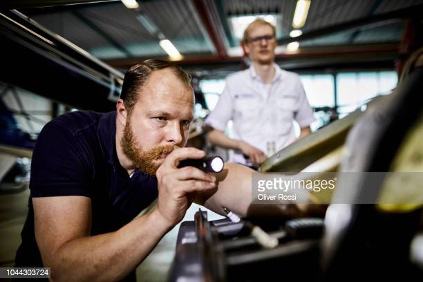 focused mechanic with flashlight working on machine part in airplane hangar - inside helicopter stock pictures, royalty-free photos & images