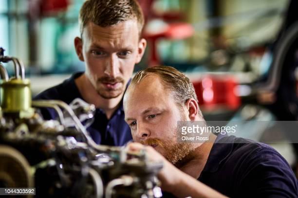 focused mechanics working on helicopter engine in airplane hangar - techniker stock-fotos und bilder