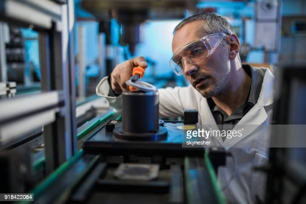 Focused mid adult engineer working on machinery in laboratory.