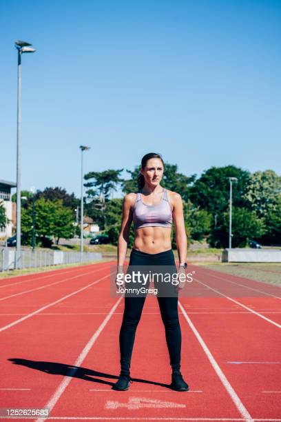 focused mid adult female runner standing on sports track - legs apart stock pictures, royalty-free photos & images
