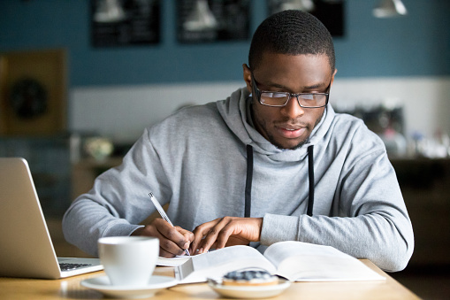 Focused millennial african student making notes while studying in cafe 962315354