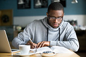 Focused millennial african student making notes while studying in cafe