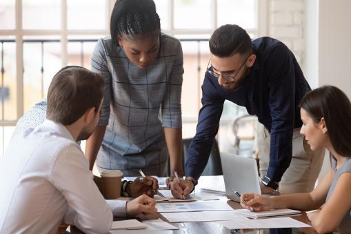 Focused multiracial corporate business team people brainstorm on paperwork 1176842719