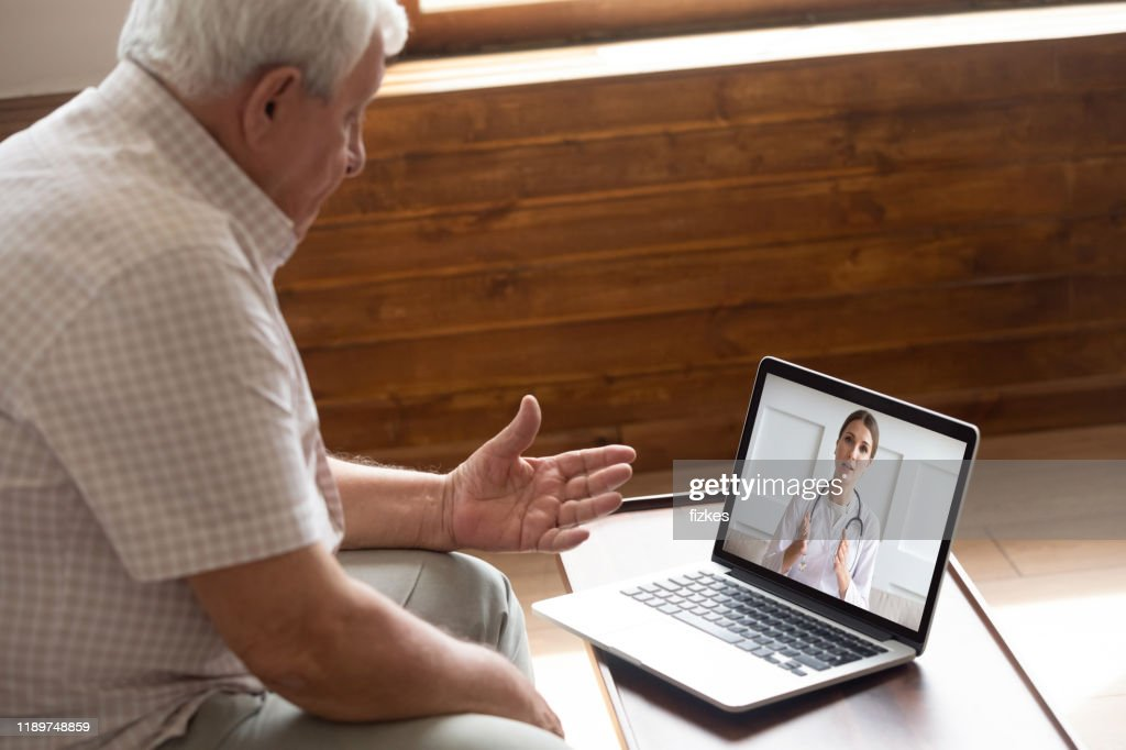 Focused older 80s patient consulting with doctor via video call. : Stock Photo