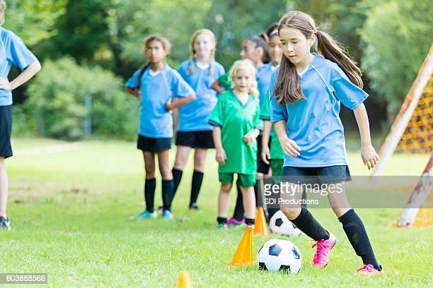Focused preteen soccer player runs through practice drills