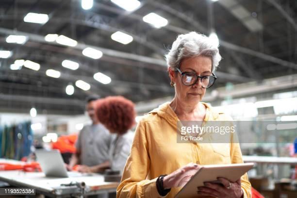 empresaria senior enfocada usando tabletas digitales y trabajando en una fábrica - equidad de genero fotografías e imágenes de stock
