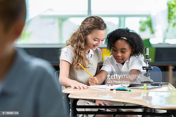 Focused STEM elementary schoolgirls work on science project