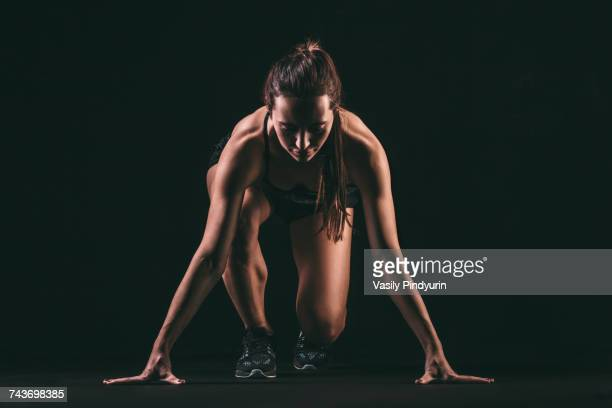 Focused woman in starting position against black background