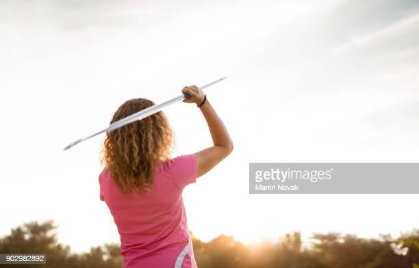 Focused - woman throwing javelin at sunset