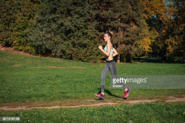 Focused woman with long legs running in forest