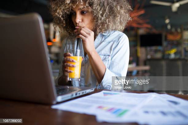 focused young african woman working online in a cafe - orange juice stock pictures, royalty-free photos & images