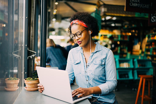 Focused young African woman working online in a cafe 833170576