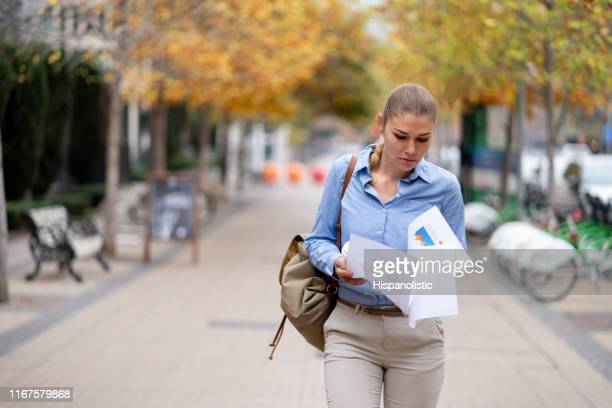 Focused young businesswoman going over some documents while walking to the office