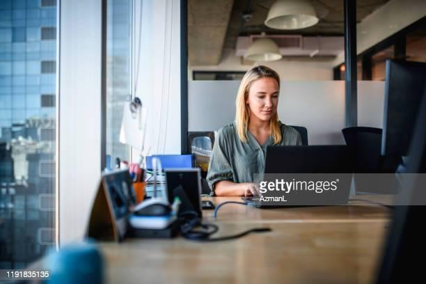 gerichte jonge zakenvrouw werken aan laptop in office - working stockfoto's en -beelden