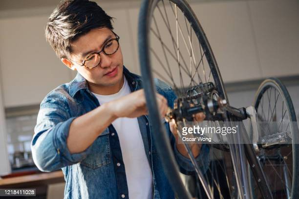 focused young man repairing bicycle at home - adjusting stock pictures, royalty-free photos & images