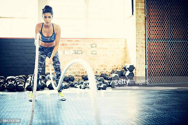 Focused young woman exercising with battling ropes in gym