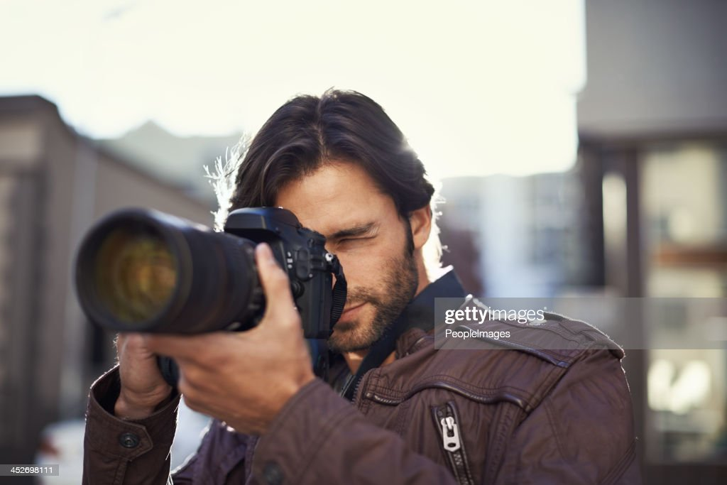 Focusing on his photography skills : Stock Photo