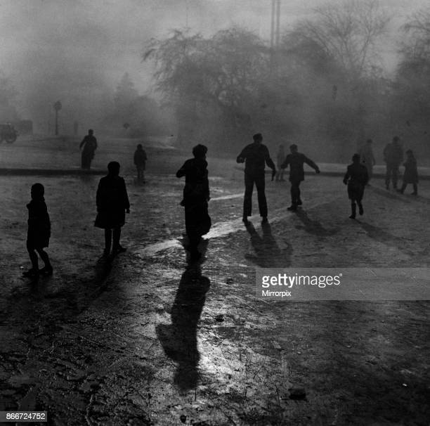 Fog and ice on Hampstead Heath. Boys sliding on the ice in the fog at Hampstead Heath ponds. Although the weather was wintry and the fog was thick,...