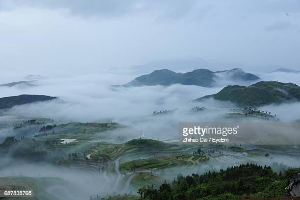 Fog Covered Fields And Mountains