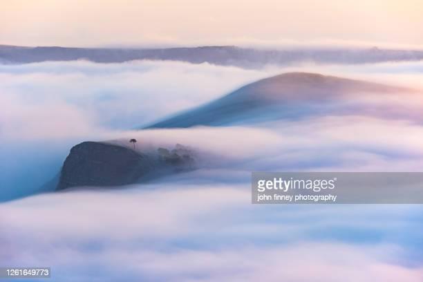 fog creeping over hills at sunrise, castleton, peak district. uk - idyllic stock pictures, royalty-free photos & images