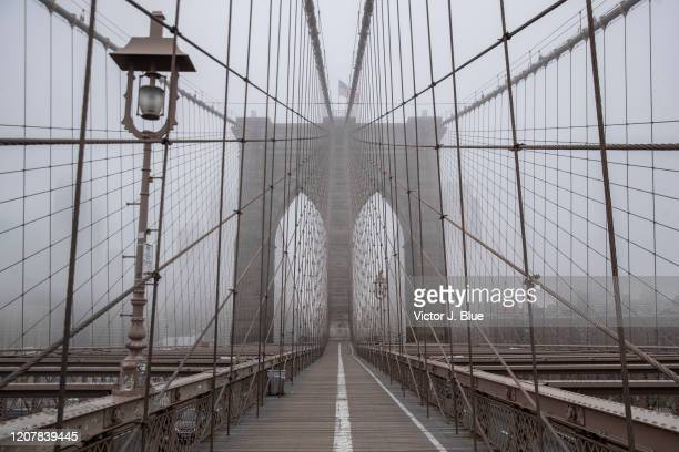 Fog envelops the Manhattan skyline as the Brooklyn Bridge sits nearly empty of pedestrian traffic in the midst of the coronavirus outbreak on March...