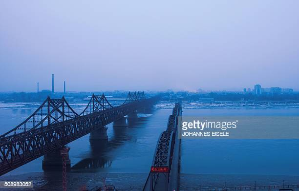 TOPSHOT Fog is seen on the banks of the Yalu River in the Chinese border town of Dandong opposite to the North Korean town of Sinuiju on February 8...