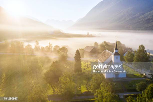 fog over church of stryn at sunrise, norway - church stock pictures, royalty-free photos & images