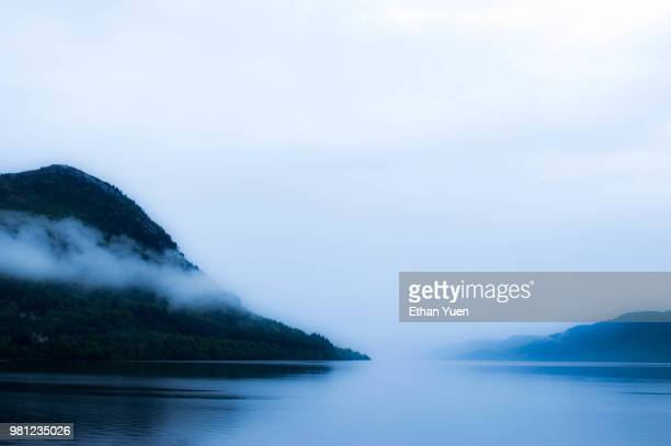 fog over lake among forest covered hills, highlands, scotland, uk - loch ness stock photos and pictures