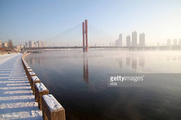 Fog rises from the water of Songhua River after a powerful cold front swept across the city on November 25 2016 in Jilin Jilin Province of China...