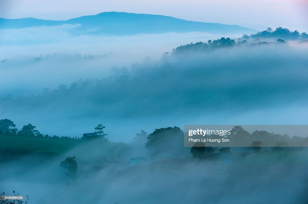 Fog rolling in the hill with farmer houses : Stock Photo