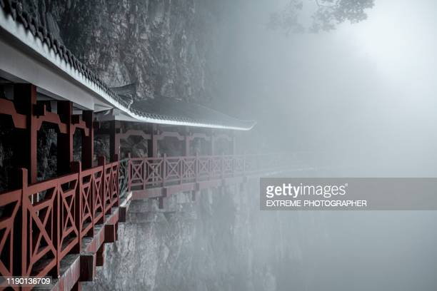 fog-covered footpath archways hanging off on a steep cliffside on tianmen mountain (天门山), zhangjiajie (张家界), china - tianmen stock pictures, royalty-free photos & images