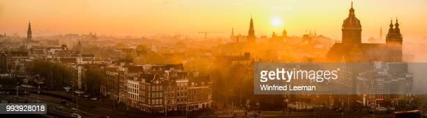 Foggy Amsterdam city center at sunset